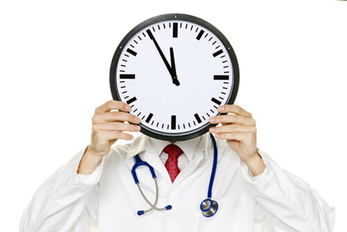 Doctor holding clock